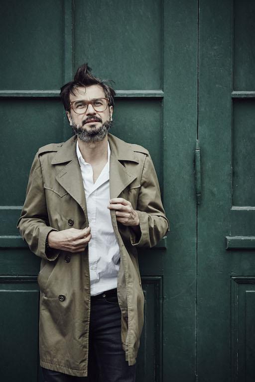 Portrait Mario Lombardo im Trenchcoat vor grüner Tür