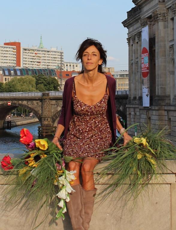 Gaby Haiber im Blumenkleid mit Blumensträußen auf der Mauer am Bodemuseum in Berlin